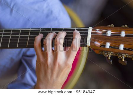 Acoustic Guitar's Fretboard And Young Male's Hand