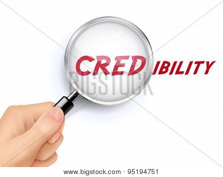 credibility word showing through magnifying glass held by hand poster