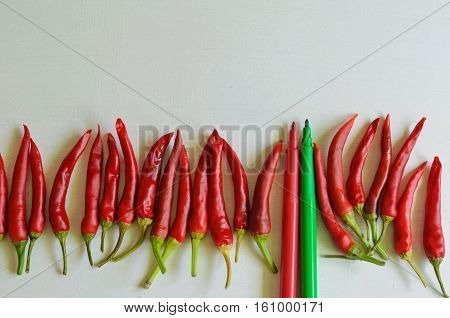 Hot chili peppers and green and red felt pens on white background