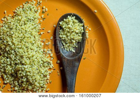 Hemp seeds healthy food on an orange ceramic plate with a wooden spoon