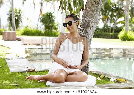 Sweet Shot Of Attractive Young Woman Expecting Child Sitting Under Tree, Enjoying Happy Moment Of He