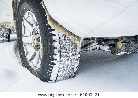 Closeup of 4x4 SUV car wheels driving on snow