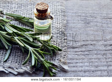 Rosemary essential oil in a glass bottle with fresh green rosemary herb on old wooden table. Rosemary oil for spa,aromatherapy and body care. Extract oil of rosemary. Selective focus.