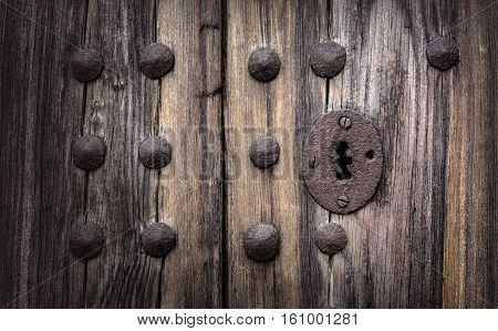 Keyhole in an old paneled wooden door; rusty and weathered. This image has been processed to make a more impactful dramatic shot.