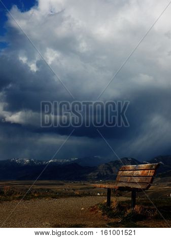 sun lit bench on hill with storm in the background