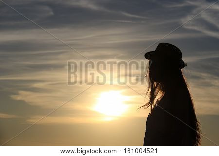 A girl's silhouette against the sun with flying golden hair she's wearing a hat.