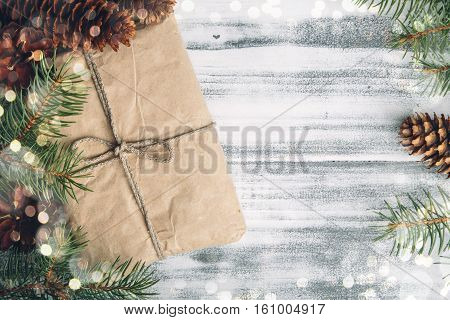 Gift wrapped craft paper with pine cones and fir branches top view copy space at the right