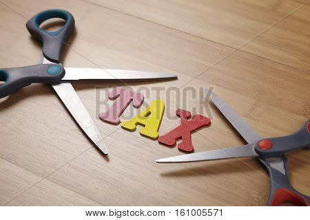 Two scissors with the word tax on the wooden background