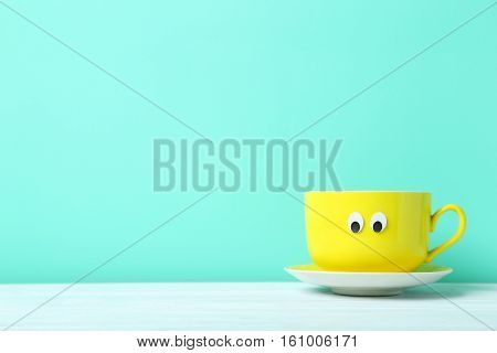Yellow Cup With Googly Eyes On A Green Background