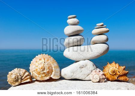 seashells and rock Zen in the form of scales on the background of sea and blue sky