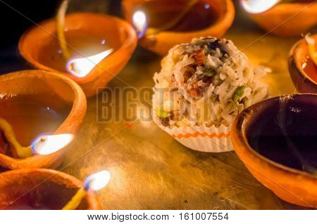 Earthenware pots with cotton wicks and oil, diya, used for lighting. These are used in diwali for celebration and decoration. Pictured along with indian traditional sweets