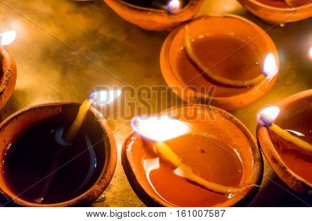 Earthenware pots with cotton wicks and oil, diya, used for lighting. These are used in diwali for celebration and decoration.
