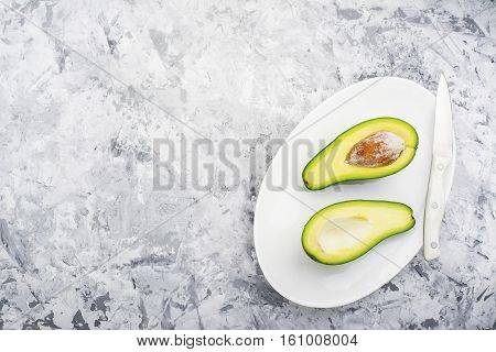 The half of a ripe avocado on an oval plate on a gray marble background. Top view. Color year. Greenery