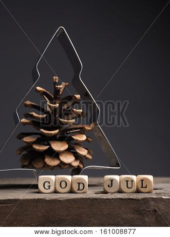 Christmas tree shape with pine cone and wooden dices with the words God Jul Scandinavian Merry Christmas