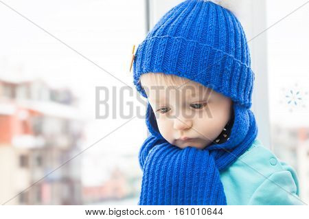 Sick child in warm clothes with sad look during winter holidays in house opposite window, wishing to go walking