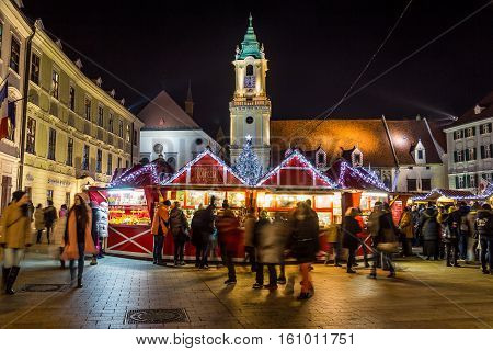 BRATISLAVA SLOVAKIA - 4TH DECEMBER 2016: Stara radnica and Bratislava Christmas Market at night. The Blur of people can be seen.