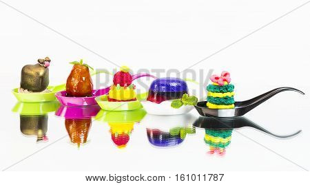 Molecular cuisine desserts in plastic spoon on a white background