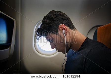Side view of handsome young man against plane window sitting and listening to music with headphones.