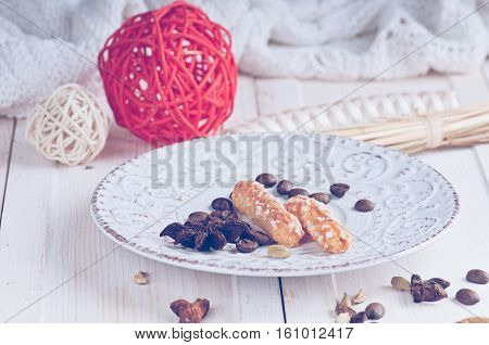 a sugar cookies on a vintage saucer with ornament balls and spice anisetree and cardamom on a white surface and a knitted blanket in the background haze filter.