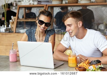 Attractive Smiling Woman Wearing Trendy Shades Showing Something On Laptop Computer To Her Handsome