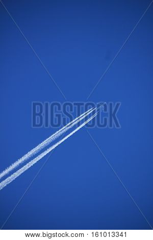 Contrails of a big airplane in a clear blue sky