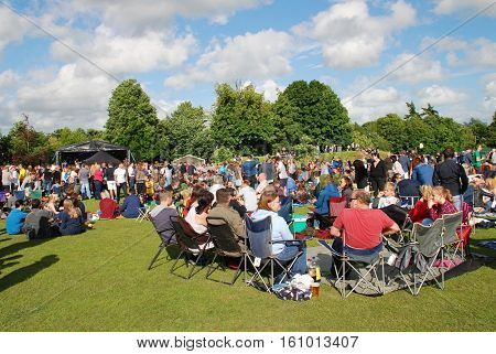 TENTERDEN, ENGLAND - JULY 2, 2016: The audience sits on the grass during the annual Tentertainment music festival. Held in the public park the free community event first took place  in 2008.