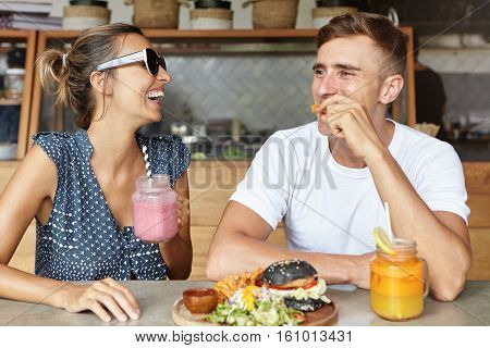 Two Best Friends Having Fun Together And Laughing While Eating Lunch At Coffee Shop. Attractive Fema