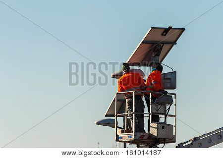 Workers in lift bucket during the maintenance of streetlight powered by a solar panel.