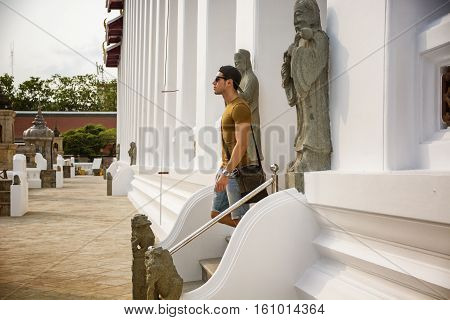 Side view of young man walking down stairs of buddhist temple in Bangkok, Thailand and looking straight.