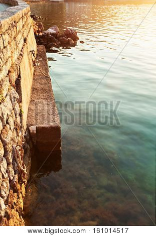 fragment of a stone embankment snd sea at sunset time.  Montenegro