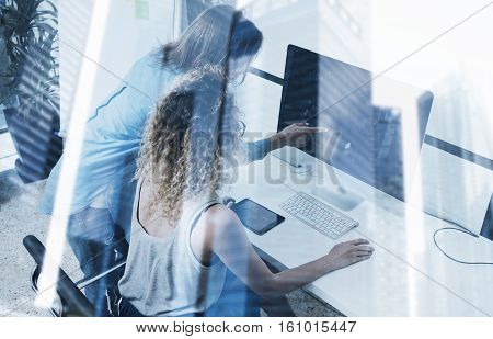 Two young girl working on computer in modern coworking studio.Coworkers using electronics gadgets.Icons, graphs and diagramm monitor.Double exposure, skyscraper building, blurred background.Horizontal