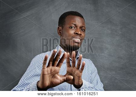 African Man With Scared Expression On His Face Making Frightened Gesture With His Palms As If Trying