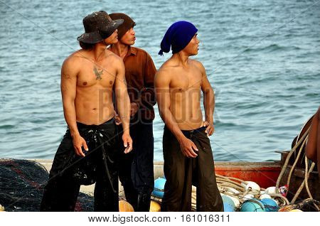 Hua Hin Thailand - December 31 2009: Three muscular young Thai fishermen standing on a boat docked at the Hua Hin fishing pier (S)