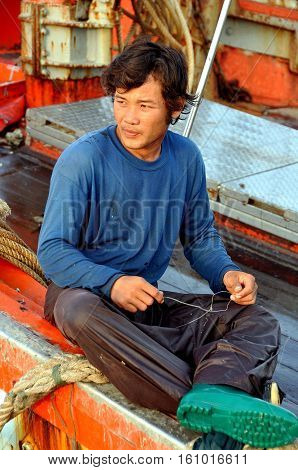 Hua Hin Thailand - December 30 2009: Thai fisherman on his boat docked at the Hua Hin fishing pier mending nets used during a day at sea