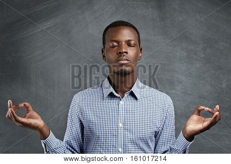 Attractive Dark-skinned Businessman With Peaceful Expression Meditating, Holding His Hands In Mudra
