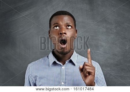 Headshot Of Puzzled And Amazed Dark-skinned Customer Dressed In Stylish Shirt Looking Up In Shock An