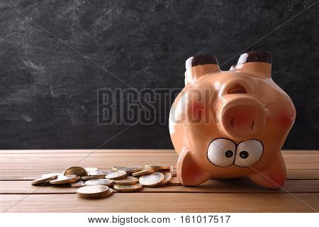 Concept Of Spending The Savings With Piggy Bank Upside Down