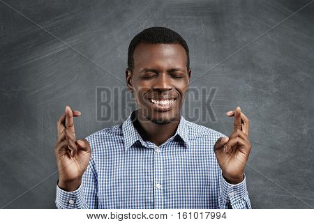 Handsome African Student In Checkered Shirt Crossing His Fingers On Both Hands And Keeping Eyes Shut