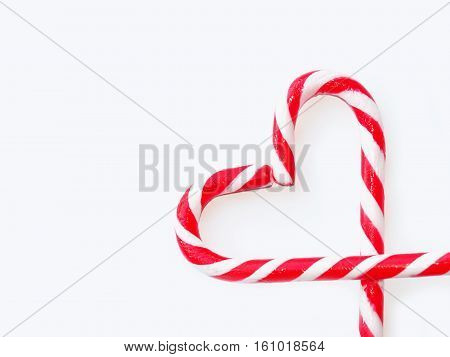 Traditional Christmas candy - candy cane shepherd's staff decorated with red and white stripes. Sandy Cane heart shaped background