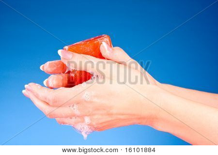 Hands with soap on blue background