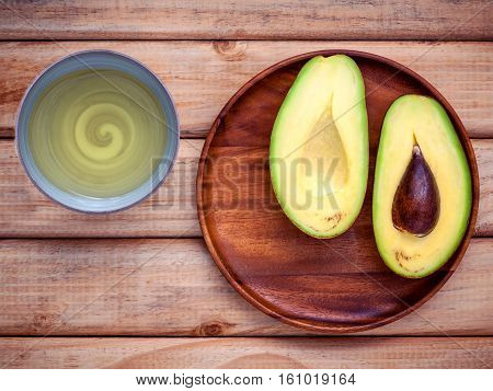 Healthy Food Concept. Fresh Avocado In Wooden Plate On Shabby Wooden Background With Avocado Oil In