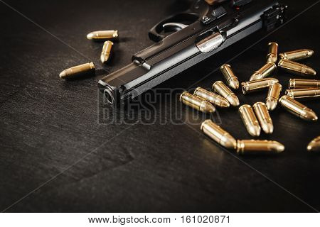 black pistol and cartridges on a black wooden table