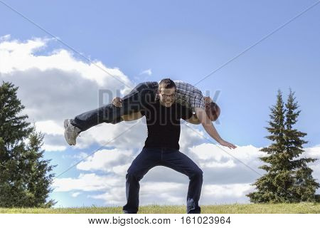 horizontal image of a well built caucasian teen age guy carrying his dad across his shoulder gritting his teeth in the summer with a blue sky  over head.