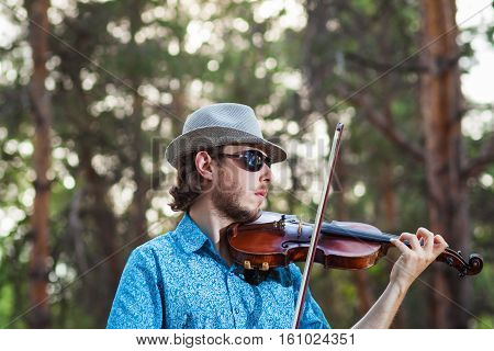 Musician playing the violin in the forest