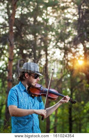 Violinist playing the violin in the forest