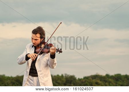 Violinist playing the violin outdoors close up horizontal