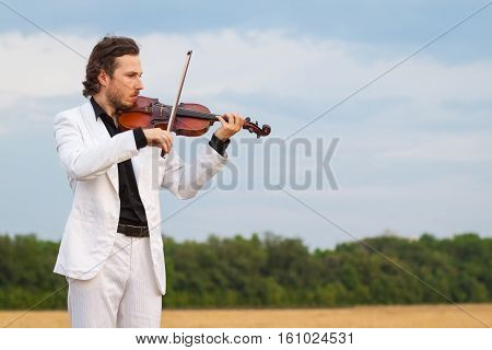 Professional violinist playing the violin outdoors close up horizontal