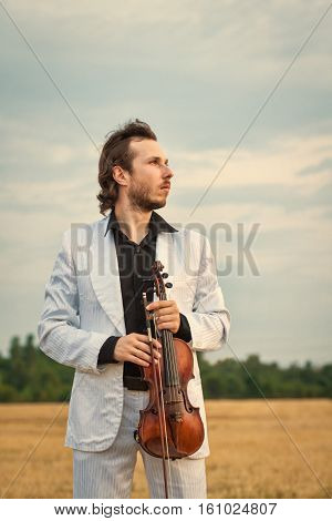 Professional violinist with the violin outdoors close up vertical