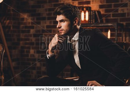 Portrait Of Ponder Man In Suit  Sitting On Couch And Touching Chin