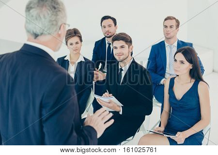 Group Of Happy Colleagues Listening To Report Of Their Boss